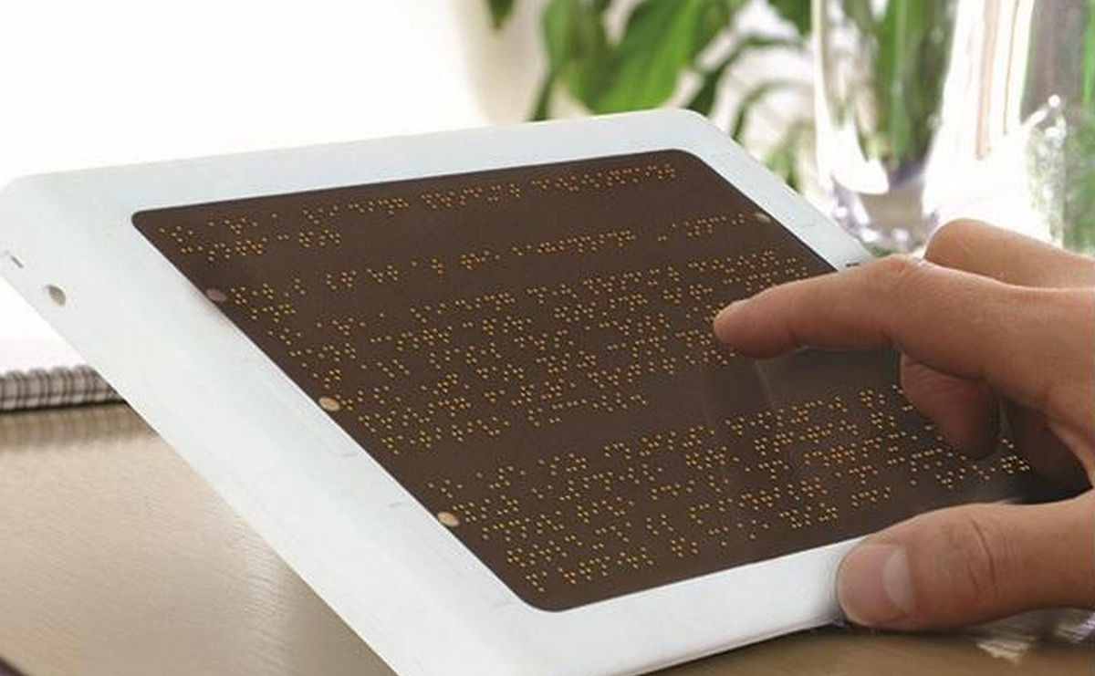 Braille display converting a website's text to braille with user's fingers running over it.